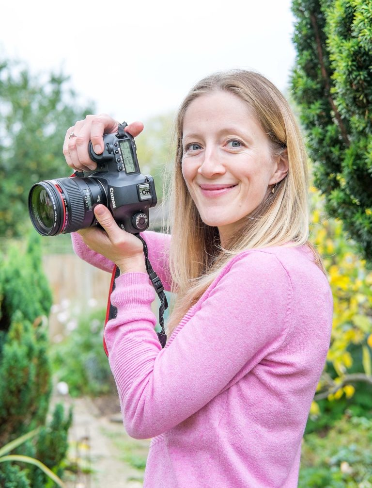 Female photographer holding camera and smiling