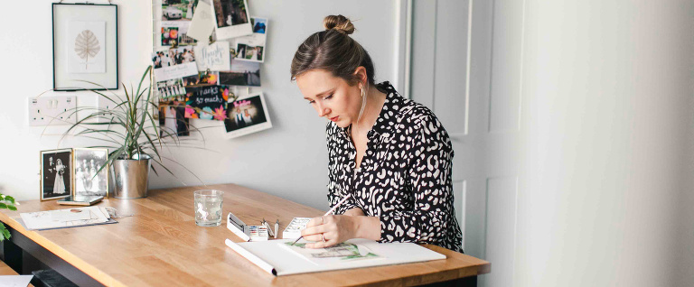 Woman doing watercolour painting sitting at a wooden desk