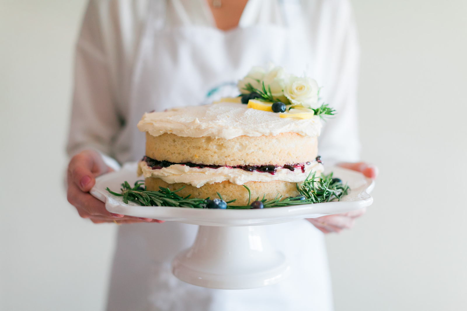 Chef in a white apron holding freshly baked vegan cake decorated with flowers and fruit