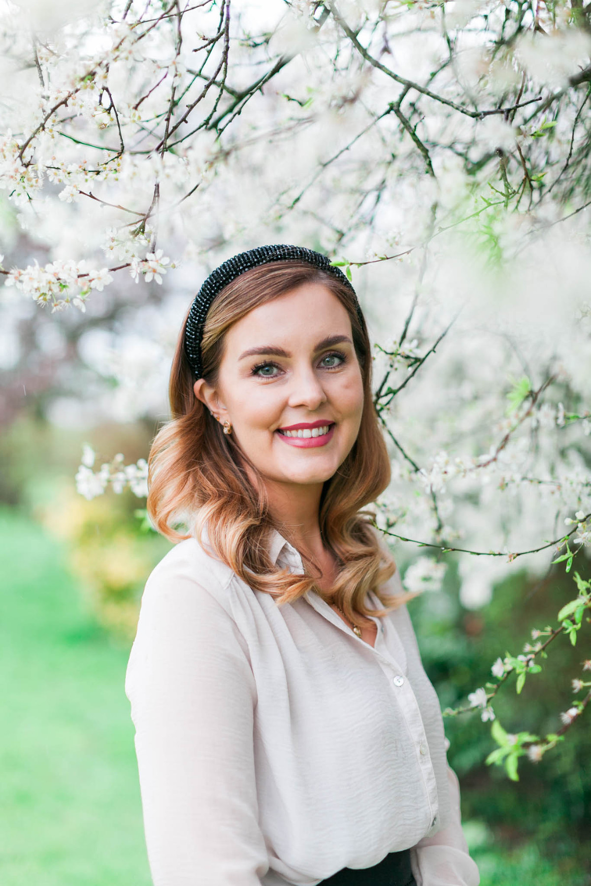 Branding photo for Cotswold wedding make up artist standing amongst spring blossom by Emma Jackson Photography