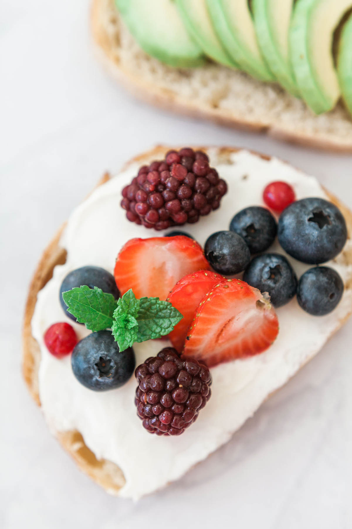 Food photography showing gourmet toasts - berries and cream cheese on toast