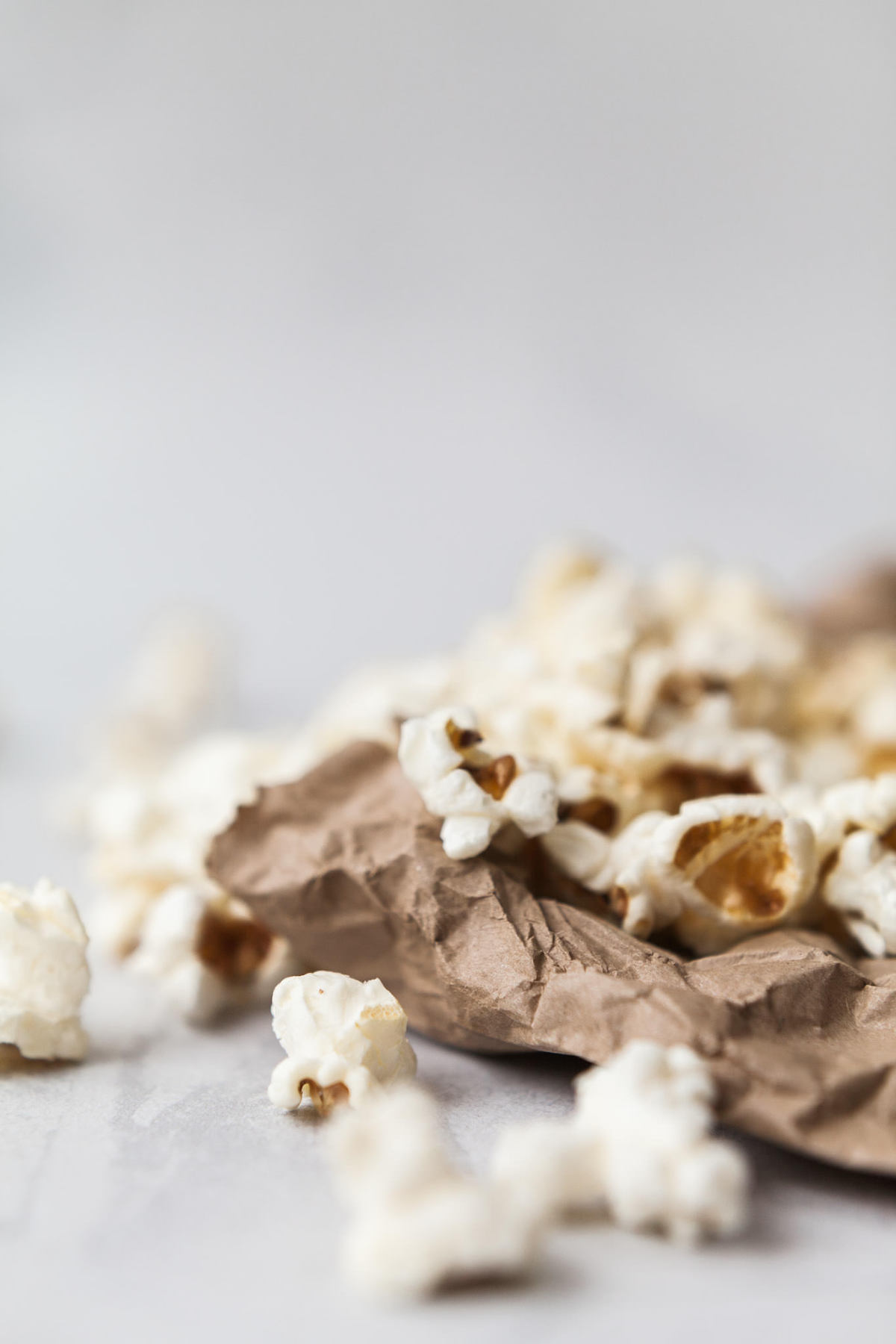 Food photography showing popcorn scattered over a brown paper bag