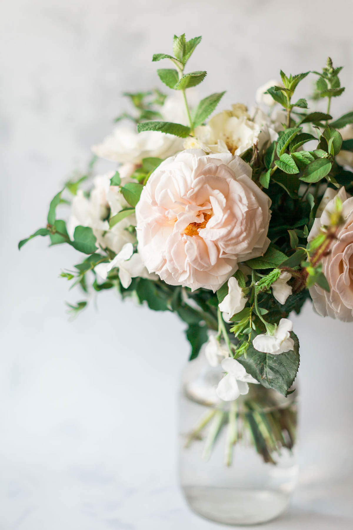 Product photography showing a bouquet of blush flowers and greenery in a mason jar