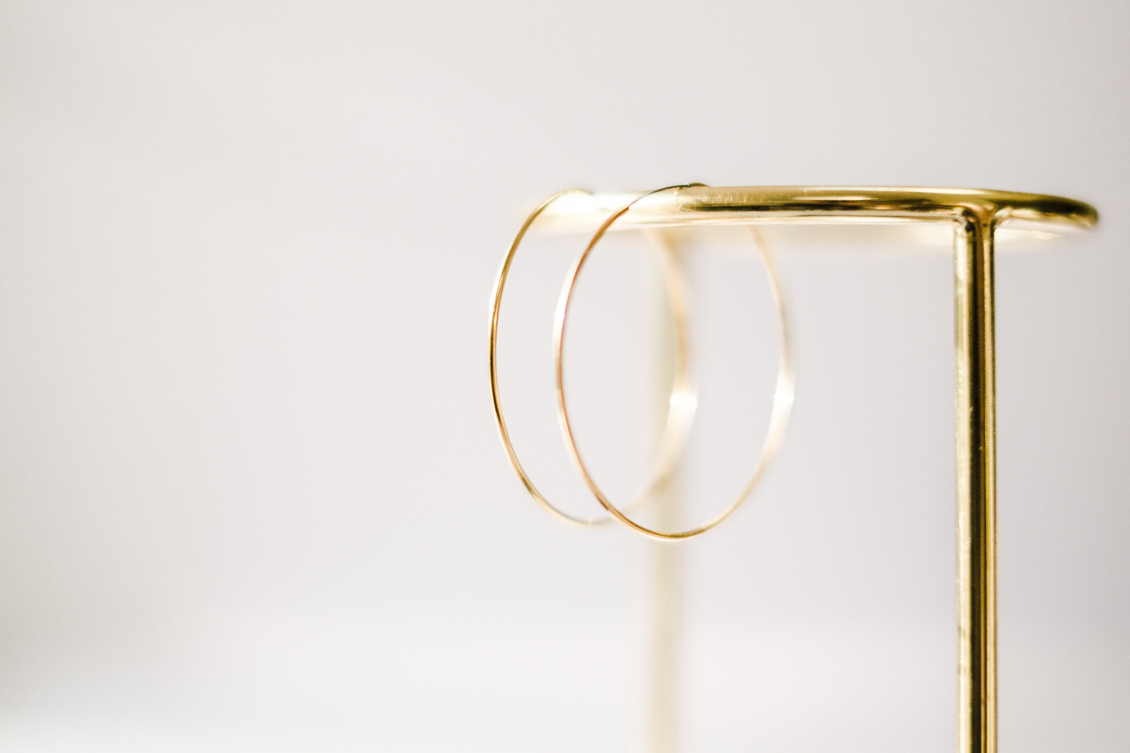 Delicate gold hoops hanging on a gold jewellery stand as part of a product shoot