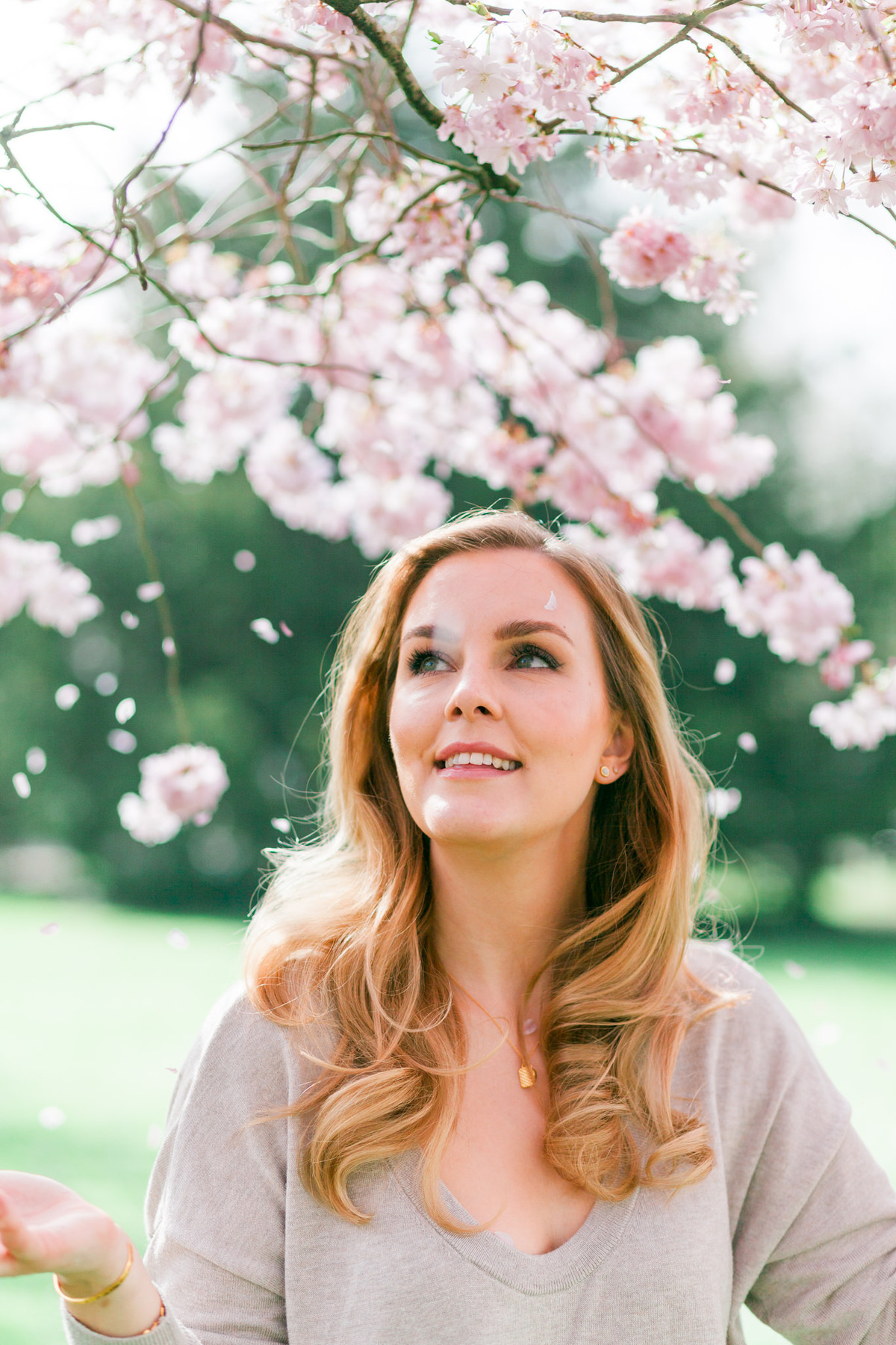 Branding headshot photo by Emma Jackson Photography of a woman in a neutral top standing amongst pink blossom watching the petals fall