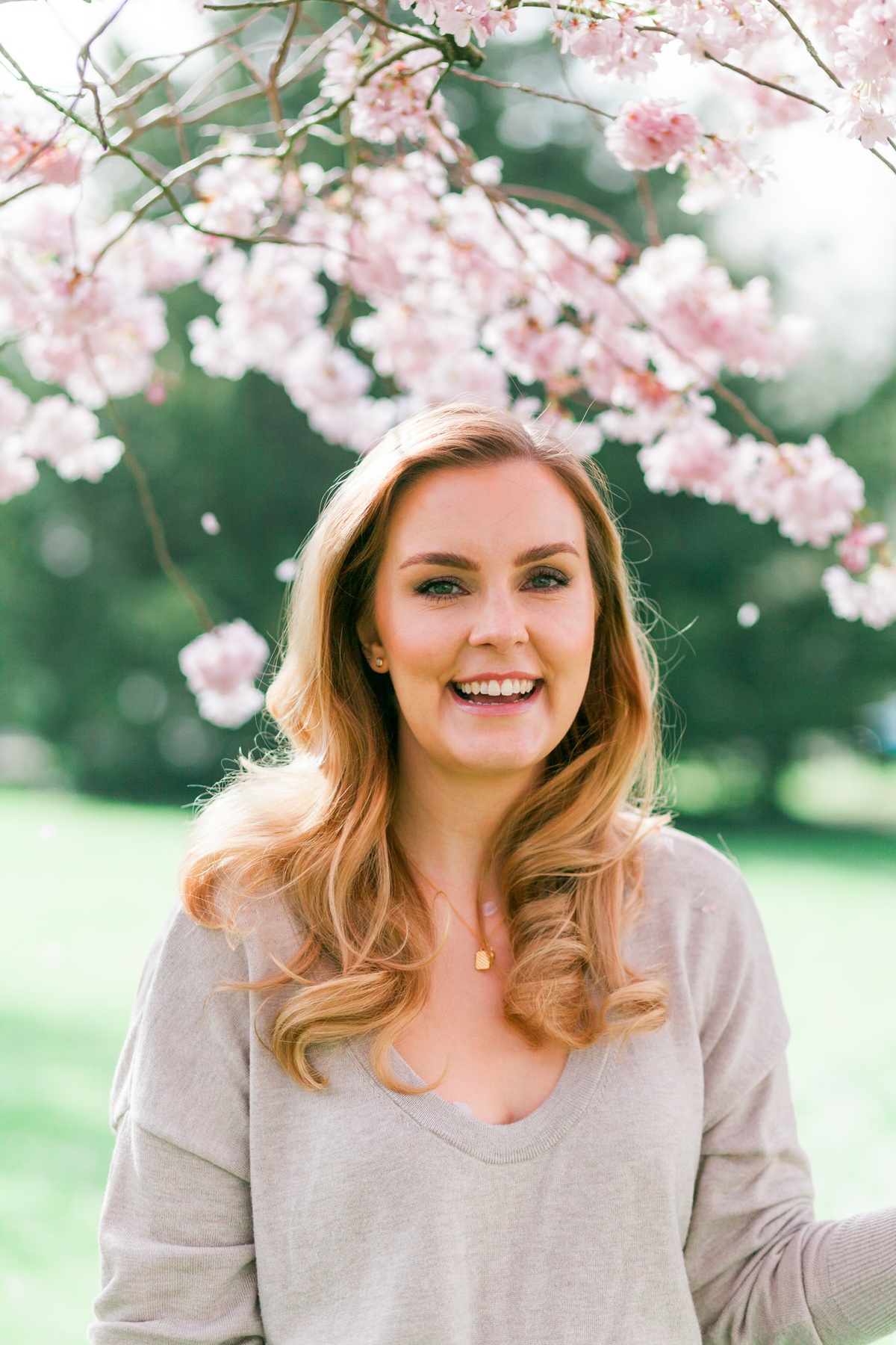 Branding headshot photo by Emma Jackson Photography of a woman in a neutral top standing amongst pink blossom smiling