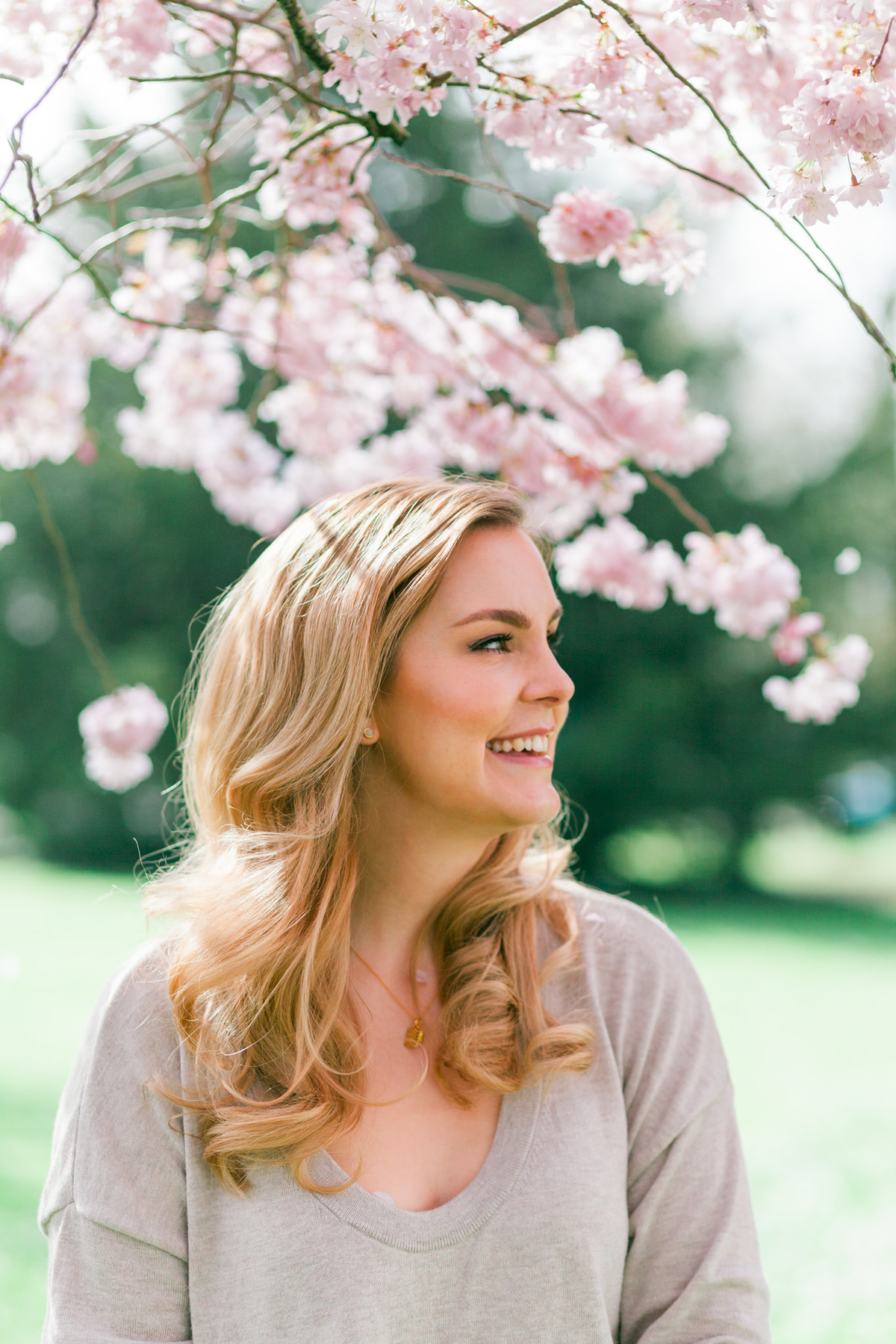Branding headshot photo by Emma Jackson Photography of a woman in a neutral top standing amongst pink blossom laughing