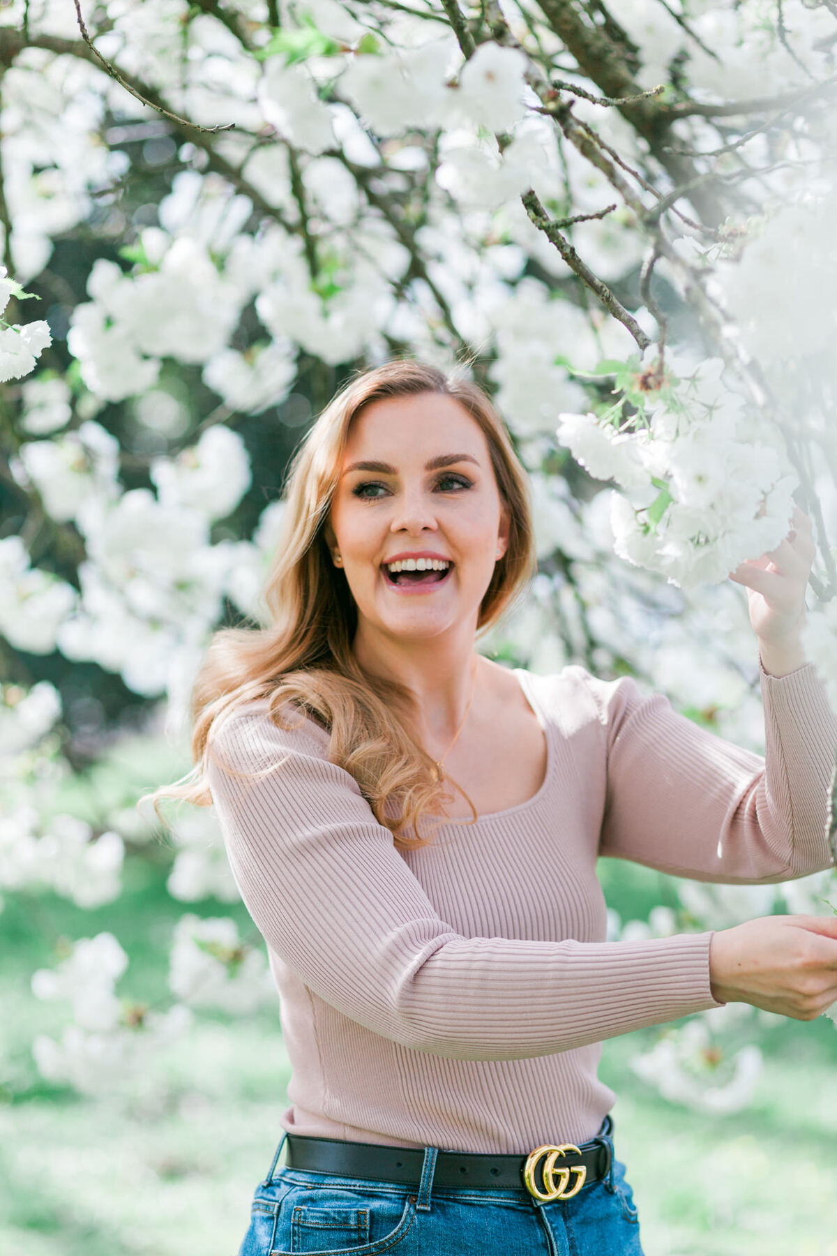 Branding headshot photo by Emma Jackson Photography of a woman in a neutral top standing amongst white blossom laughing