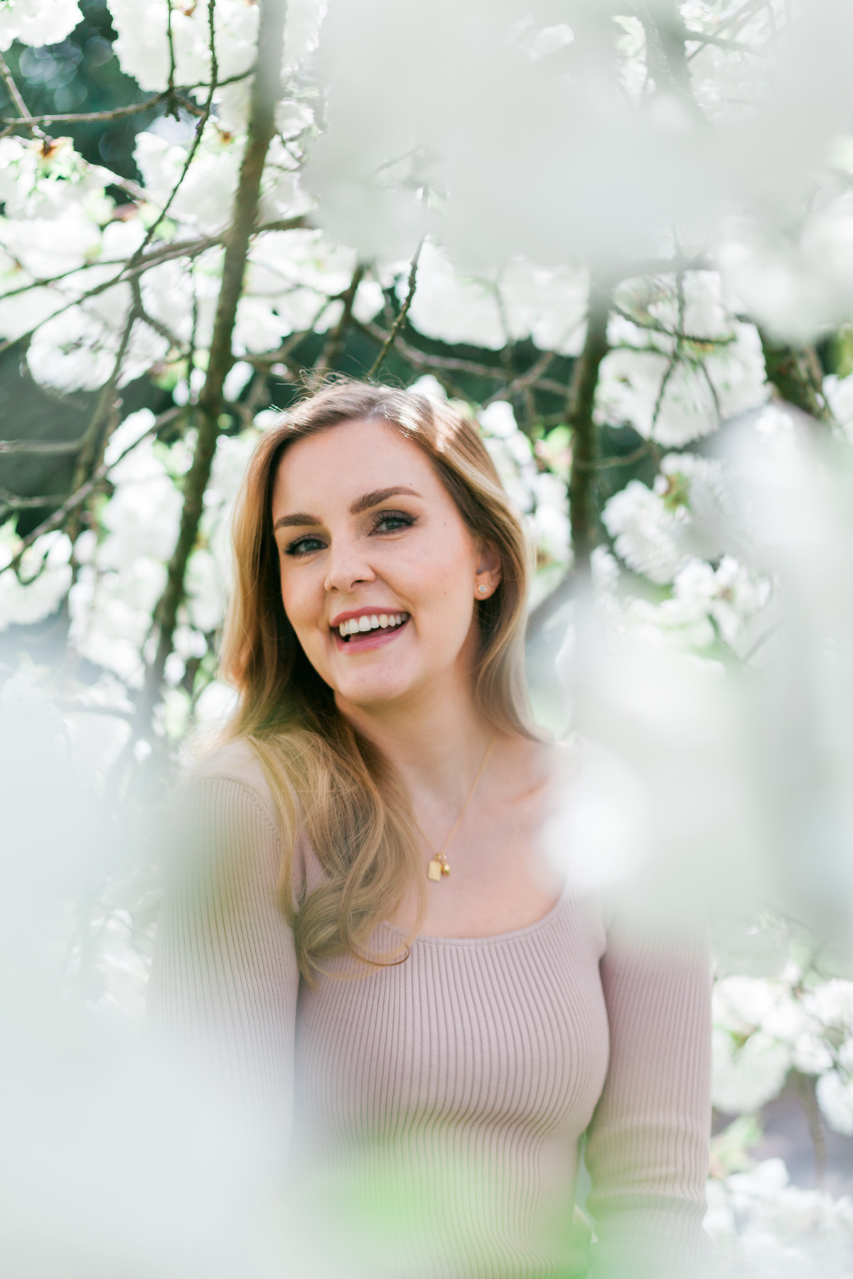 Branding headshot photo by Emma Jackson Photography of a woman in a neutral top standing amongst white blossom smiling
