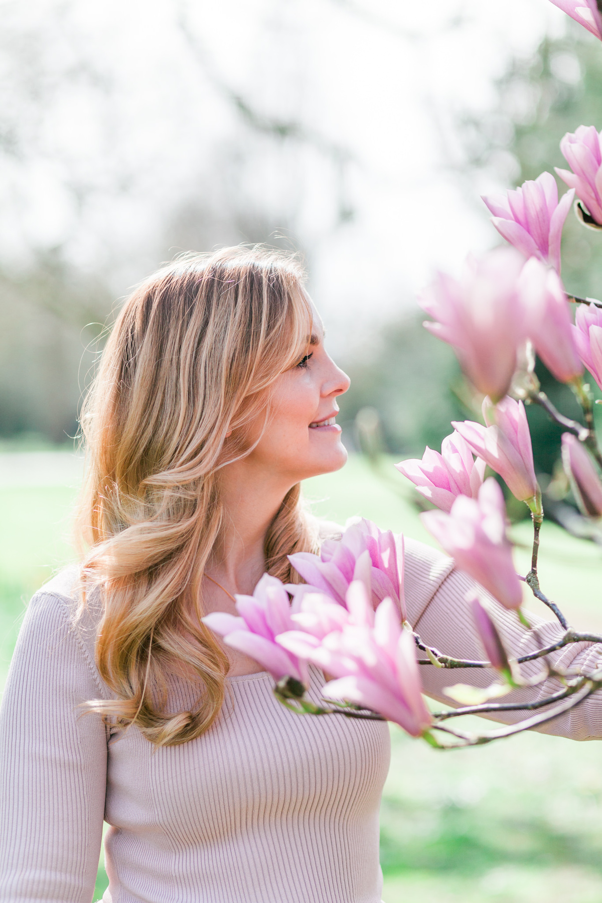 Branding headshot photo by Emma Jackson Photography of a woman in a neutral top standing amongst pink magnolia flowers smiling